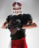American football player posing with ball on white background. Caucasian fitness man as american football player holding a ball on white background Stock Image