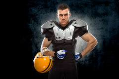 American football player. Posing in front of dark background Stock Photos