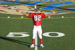 American football player, in red football strip and protective helmet, standing on pitch at 50 yard line, arms out, smiling, front Royalty Free Stock Photo