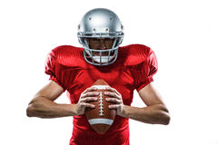 American football player in red jersey and helmet holding ball Stock Photo