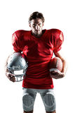 American football player in red jersey holding helmet and ball. Portrait of an American football player in red jersey holding helmet and ball on white background Stock Photo