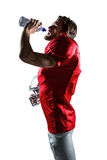 American football player in red jersey holding helmet while drinking water Stock Photo