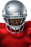 American football player in red jersey looking down. Close-up of American football player in red jersey looking down against white background Stock Image