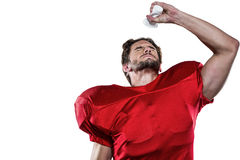 American football player in red jersey pouring water on face Stock Image