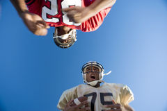 American football player running with ball at opposing player during competitive game, upward view Stock Photos