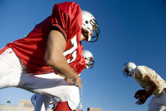 American football player running with ball at opposing team during competitive game, side view, low angle view Stock Photography