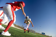 American football player running with ball at opposing team during competitive game (surface level, tilt) Stock Photos