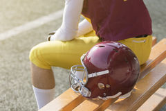 American football player sitting on bench and sports helmet next royalty free stock photos