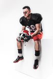 American football player sitting with  helmet on white background Royalty Free Stock Photography
