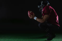 American football player sitting on toes holding a ball with both his hands. On artificial turf Royalty Free Stock Photos
