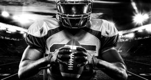 American football player, athlete in helmet with ball on stadium. Black and white photo. Sport wallpaper with copyspace. royalty free stock images