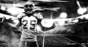 American football player, athlete in helmet on stadium. Black and white photo. Sport wallpaper with copyspace. American Football player on stadium with smoke royalty free stock photo