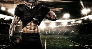 American football sportsman player on stadium. Sports banner and wallpaper with copyspace. American Football player on stadium with smoke and lights Royalty Free Stock Image