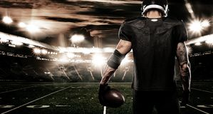American football sportsman player on stadium. Sports banner and wallpaper with copyspace. American Football player on stadium with smoke and lights Royalty Free Stock Photos