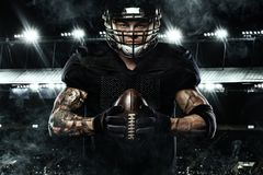 Sport concept. American football sportsman player holding ball on stadium. American Football player on stadium with smoke and lights Stock Photography