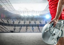 American football player standing with helmet against digitally composite stadium. Mid-section of american football player standing with helmet against digitally Stock Photos