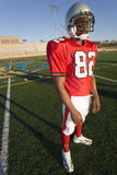 American football player standing on pitch in red football strip and protective helmet, portrait Stock Images