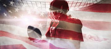 Composite image of american football player standing with rugby ball and helmet stock images