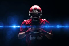 American football player standing with rugby helmet and ball. Against black background royalty free stock image
