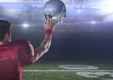 American football  player standing in stadium holding up helmet Royalty Free Stock Images