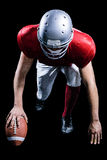American football player taking position while holding ball Royalty Free Stock Images