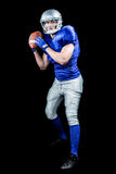 American football player throwing ball over black background Royalty Free Stock Photo
