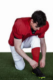 American football player tying his shoelaces Royalty Free Stock Image