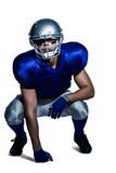 American football player in uniform crouching. Against white background Stock Image