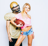 American football player in uniform and helmet posing with beautiful long-legged blond girl cheerleader dressed in a T stock photos