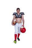 American football player walking with a ball and helmet Royalty Free Stock Photography