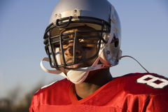 American football player wearing red football strip and protective helmet, close-up, portrait Royalty Free Stock Image