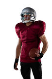 American football player wearing sports helmet. While standing against white background Stock Image