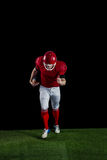 American football player wrestling through and protecting football Royalty Free Stock Photography