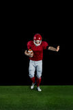 American football player wrestling through and protecting football Stock Photos