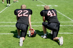 American football players. Two american football players kneeing at the sideline of the matchfield and waiting for their participation in the game stock photography