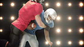 American football players against flashing lights stock footage