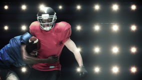 American football players against flashing lights. In slow motion stock video
