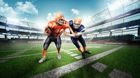 American football players on green grass. Professional american football players in the action on stadium Stock Photos