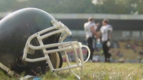 American football players having break on field, drinking water, communicating stock video