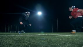 American football players jump on a football field, side view. stock video