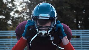 American football players preparing helmets. Slow motion of American football players preparing protective helmets before game on field stock video