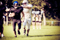 American Football Players Running. Towards the goal line, cheerleaders rooting in the background Stock Photography