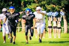American football players running. Towards the goal line, cheerleaders rooting in the background Stock Images