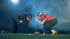American football players standing in a pose near a ball, side view. stock video footage