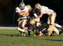 American Football Players Tackle During a Game
