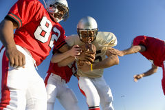 American football players tackling opposing player with ball, low angle view Royalty Free Stock Photo