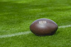 American football, rugby ball on green grass field background stock images