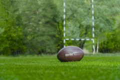 American football, rugby ball on green grass field background stock photo
