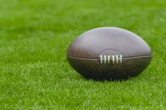 American football, rugby ball on green grass field background royalty free stock photo