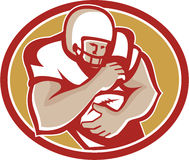 American Football Running Back Oval Retro. Illustration of an american football gridiron running back player running with ball facing front fending set inside Stock Photos